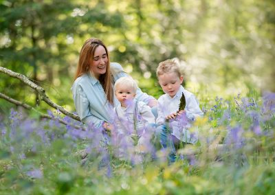 family photographer Barnsley, mum and sons playing with bark in bluebells