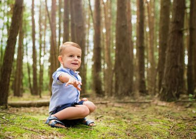 Family photographer Barnsley, boy playing with acorns in woodland