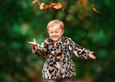 Family photographer in Barnsley, baby playing with leaves in autumn