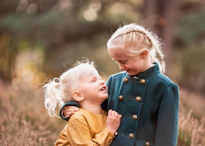 sisters cuddling at an autumn family photoshoot in Barnsley
