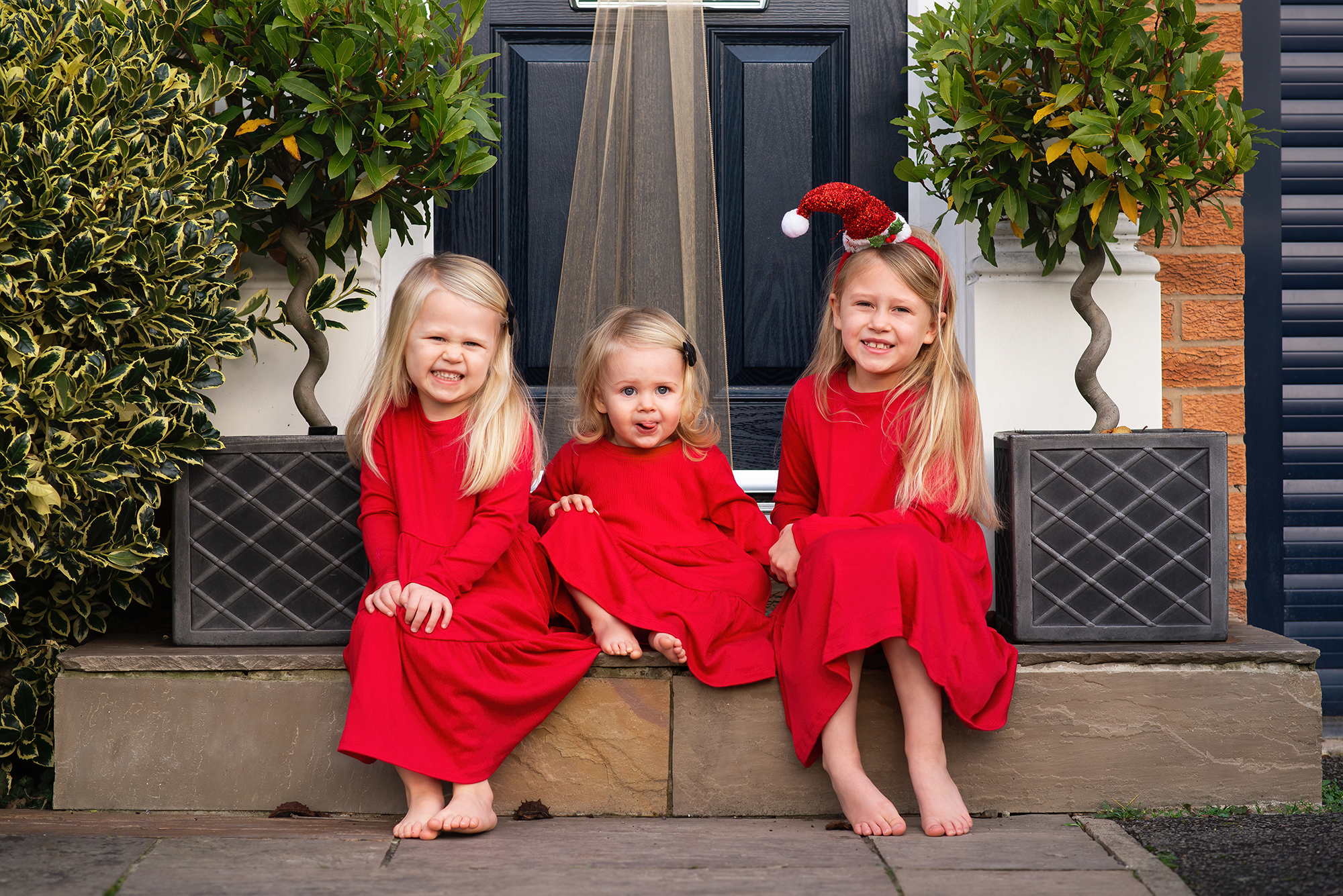 Family photographer Barnsley, girls at front step in red dresses