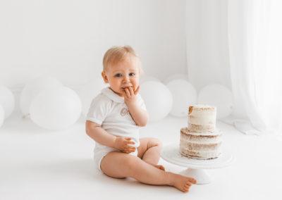 Baby enjoying cake at an all white cake smash session Barnsley