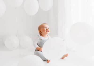 Baby boy playing with balloons at cake smash session in Barnsley