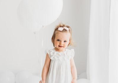 Baby girl standing with balloons at Barnsley Cake Smash photography session