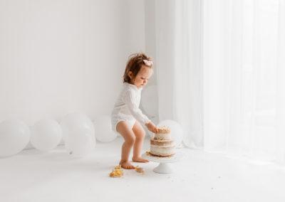 Cake smash photographer Barnsley, baby standing whilst eating cake