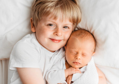 Big brother cuddling baby brother at Barnsley newborn photography session