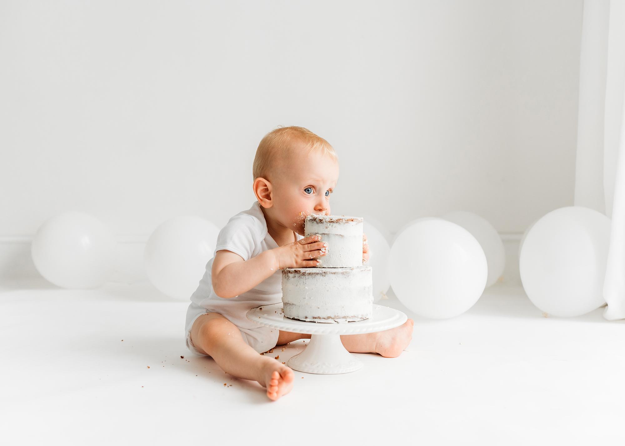 cake smash photographer Barnsley, baby biting the cake